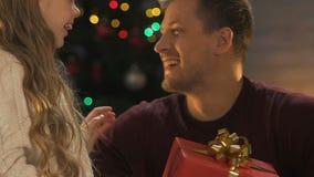 Weinig dochter die Kerstmisgift voorstellen aan vader, leuk meisje die houdende van papa koesteren stock footage