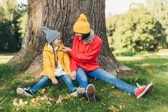 Weinig dochter en haar moeder hebben pret samen, gekleed warm, zitten dichtbij grote boom op groen gras, bekijken elkaar met lief royalty-vrije stock fotografie