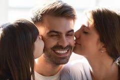 Weinig dochter en houdende van echtgenoot van de vrouwen kussende vader stock foto