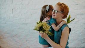 Weinig dochter koestert elkaar met bloemen stock video