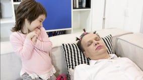 Weinig dochter past make-up op slaapvader toe stock videobeelden