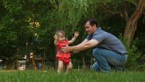 Weinig dochter treft eerste maatregelen om lachende papa op gazongras in park te ontmoeten De papa kust baby op wang en smill lan stock videobeelden