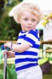 Weinig doen schrikken krullende jongen op een autoped Stock Fotografie
