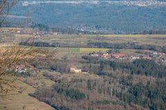Weinig dorp en weinig kasteel in het midden van het Duitse platteland met heuvels, bossen, gebieden en weiden stock fotografie