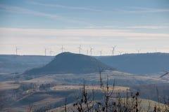 Weinig dorp en windmolens in het midden van het Duitse platteland met heuvels, bossen, gebieden en weiden stock foto