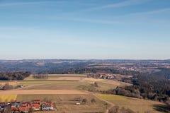 Weinig dorp in het midden van het Duitse platteland met bossen, gebieden en weiden stock afbeeldingen