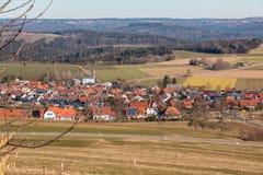 Weinig dorp in het midden van het Duitse platteland met bossen, gebieden en weiden royalty-vrije stock foto