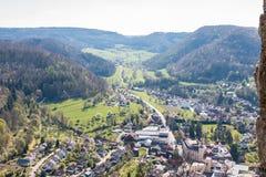 Weinig dorp in het midden van het Duitse platteland met heuvels, bossen, gebieden en weiden en de muren van een kasteel stock foto