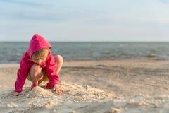Weinig drie jaar het oude meisje spelen in het zand op het overzeese strand, zonsondergang en weinig wind en, de de zomervakantie royalty-vrije stock fotografie