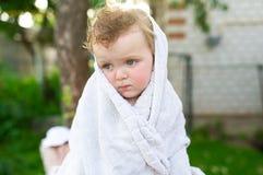Weinig droevig meisje is omhoog verpakt in een witte handdoek Stock Fotografie