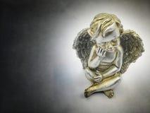 Weinig droevige engel in dark royalty-vrije stock afbeelding