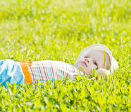 Weinig dromende baby die op het gras legt Stock Fotografie