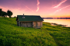 Weinig eenzaam huis op banken van de rivier bij zonsondergang in stilte Royalty-vrije Stock Fotografie