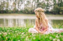 Weinig eenzame meisjeszitting in het gras door de rivier Stock Foto's