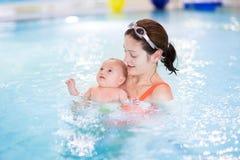 Weinig eerste keer van de babyjongen in een zwembad Stock Afbeelding
