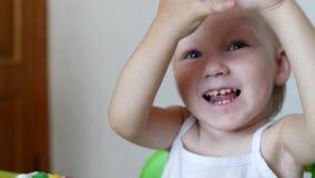 Weinig emotionele meisjeszitting bij de lijst verheugt zich en slaat, close-up, Kaukasisch portret, stock video
