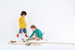 Weinig enthousiaste meisje en jongen spelen met houten spoorweg Stock Foto