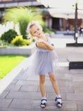 Weinig Europees mooi meisje die zich in yard bevinden en grijze kleding dragen stock foto's
