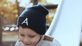 Weinig Europese jongen die onderaan een parkdia gaan Gelukkig onbezorgd mannelijk kind in hoed die pret op de speelplaats van het stock videobeelden