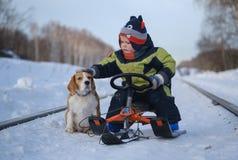 Weinig Europese zitting van de jongens petting hond op een slee in de winter royalty-vrije stock fotografie