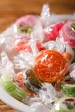 Weinig fruitsuikergoed met fruitmotieven in witte kom stock foto's