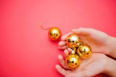 Weinig geel bont-boom stuk speelgoed in een vrouwelijke hand op een rode achtergrond stock fotografie