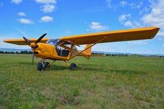 Weinig geel vliegtuig op groen grasgebied Stock Foto's