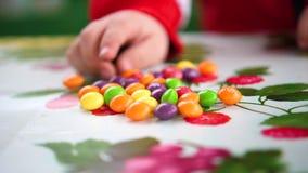 Weinig gekleurd suikergoed De kindhanden neemt suikergoed van de lijst stock footage