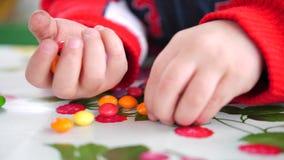 Weinig gekleurd suikergoed De kindhanden neemt suikergoed van de lijst stock video