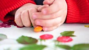 Weinig gekleurd suikergoed De kindhanden neemt suikergoed van de lijst stock videobeelden