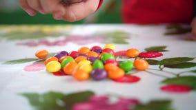 Weinig gekleurd suikergoed De kindhanden neemt suikergoed van de lijst De handen sluiten omhoog stock video