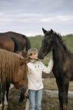 Weinig gelukkig jong meisje die zich onder paarden en veulennen in een witte sweaterjeans bevinden Levensstijlportret Stock Fotografie