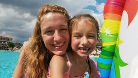Weinig gelukkig meisje zonder melktanden en haar mamma die in de pool zwemmen stock video