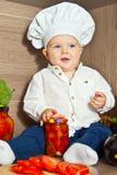 Weinig gelukkig spel van het jongensjonge geitje in chef-kok bij keuken en kokvoedsel Royalty-vrije Stock Foto