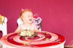 Weinig gelukkige babymeisje het vieren eerste verjaardag Jong geitje en haar eerste cake op partij Kinderjaren Royalty-vrije Stock Afbeeldingen