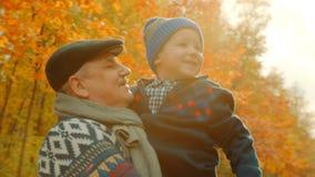 Weinig gelukkige jongen en zijn grootvader in het de herfstpark Stock Fotografie