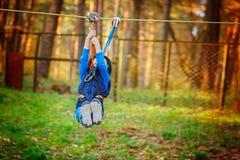 Weinig gelukkige kindjongen in avonturenpark in veiligheidsmateriaal in de zomerdag Stock Afbeeldingen