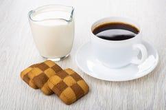 Weinig geruite zandkoekkoekjes, kop van koffie, melk op lijst royalty-vrije stock foto
