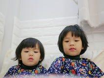 Weinig gezichten van babymeisjes, zusters, 2 en 3 jaar oud, terwijl het letten op/het staren bij een smartphone stock foto's