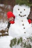 Weinig girlposing met sneeuwman Royalty-vrije Stock Foto's