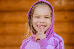 Weinig glimlachend meisje brengt wijsvinger aan lippen aan royalty-vrije stock foto
