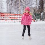 Weinig glimlachend meisje die op ijs in roze slijtage schaatsen De winter Royalty-vrije Stock Afbeelding