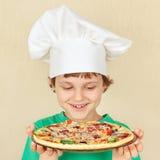 Weinig glimlachende jongen in chef-kokshoed met gekookte eigengemaakte pizza Royalty-vrije Stock Foto's