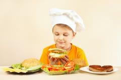 Weinig glimlachende jongen die in chef-kokshoed hamburger voorbereiden Royalty-vrije Stock Foto's