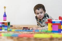 weinig glimlachende jongen die met aannemersstuk speelgoed spelen Jongen die intellectueel speelgoed spelen royalty-vrije stock afbeeldingen