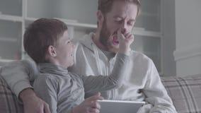 Weinig glimlachende jongen greep zijn vader door de neus en trekt het, lachen allebei Vriendschappelijk verband tussen papa stock videobeelden