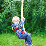 Weinig glimlachende jongen van drie jaar die pret op schommeling hebben Royalty-vrije Stock Fotografie