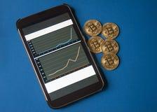 Weinig gouden bitcoins ligt op de lijst voor en naast de tablet waarop de grafieken van Bitcoins-de kostengroei zichtbaar zijn royalty-vrije stock foto's
