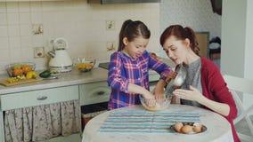 Weinig grappig meisje die haar moeder in de keuken helpen die ei bebouwen in kom en deeg voor koekjes mengen Familie, voedsel stock video