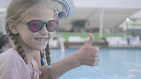 Weinig grappig meisje met vlechten en rijpe vrouwenzitting op de rand van de pool die in de camera glimlachen en duim tonen stock footage